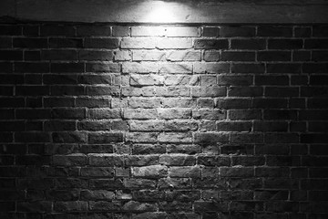 Grungy dark brick wall with spotlight