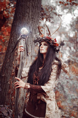 beautiful brunette with a painted face, clothes shaman, a floral wreath on her head and horns, holding a glowing wooden staff, in the woods