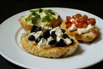 Bruschetta with feta and tomatoes, feta and black olives, feta and green onions on white plate.