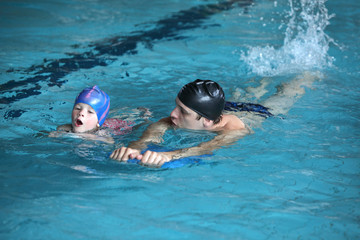 swimming lesson - child practicing flutter kick with kick board with instructor in swimming pool