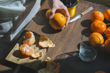 Woman hand peeling ripe sweet tangerine