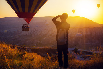 man taking picture of Hot air balloons