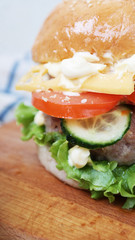 Big tasty juicy hamburger with fried meat slice of cheese with fresh leaf lettuce and vegetables