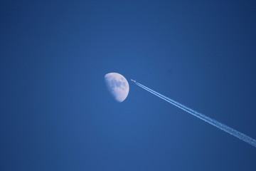 Jet airplane with trail of fuel on blue sky and big moon