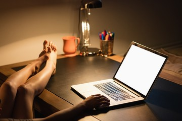 Cropped image of a woman using laptop with feet on the desk