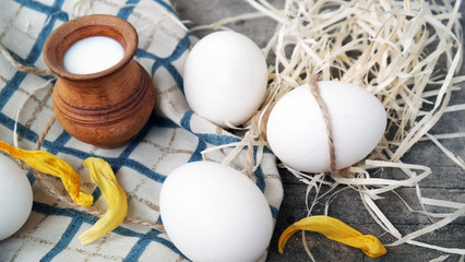 jug with fresh milk and homemade white eggs with a rope and straw on a wooden floor