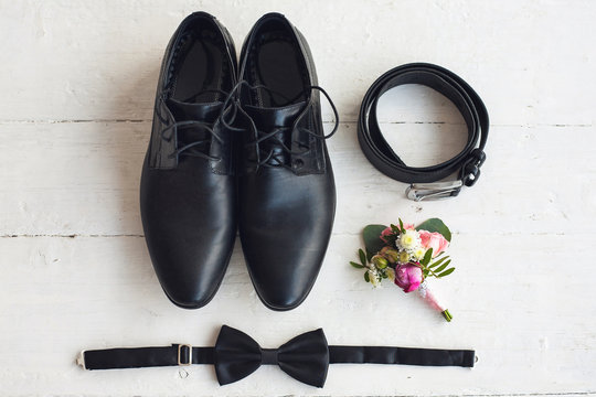 Close up of modern man accessories. Black bowtie, leather shoes, belt and flower boutonniere on white wood rustic background. Set for formal style of wearing isolated on white background.