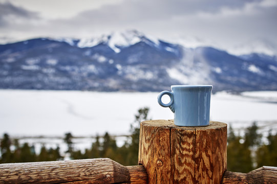 a steaming cup of coffee in the mountains