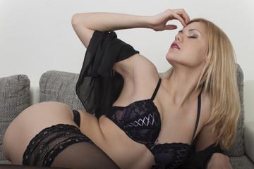 Frau in Unterwäsche auf einem Sofa