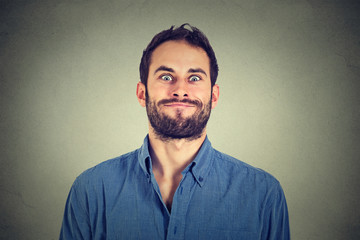 Crazy looking man making funny faces isolated on gray wall background .