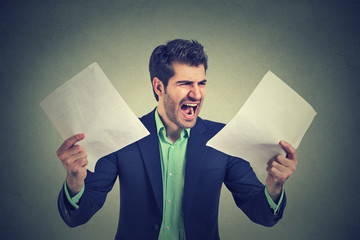 Angry stressed screaming business man with documents papers paperwork