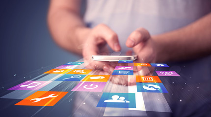Man holding smart phone with colorful application icons