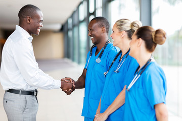 medical rep handshaking with group of doctors