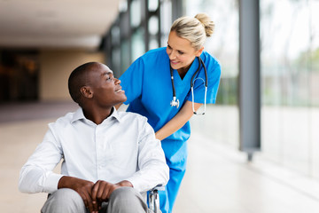 female nurse talking to disabled patient