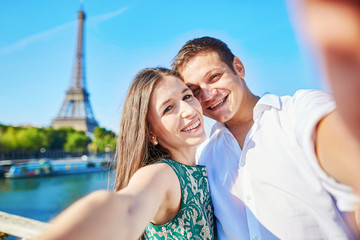 Couple having a date and taking selfie near the Eiffel tower in Paris, France