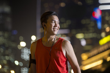 Sporty Asian man outdoors in urban city at night