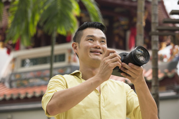 Chinese tourist using his DSLR to take a photo.