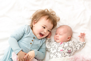 Toddler girl playing with her newborn sister