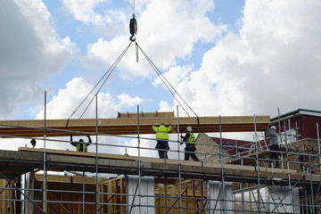 Construction workers lifting big wooden frame on a new development site