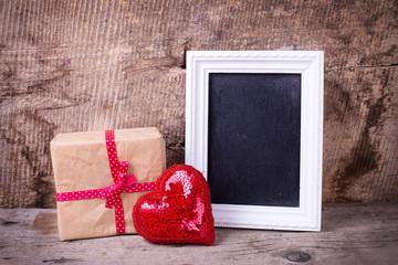 Festive gift box, decorative red  heart anrd empty blackboard  o