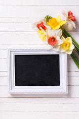 Narcissus flowers and empty blackboard  on white  painted wooden