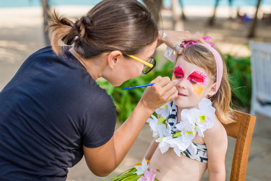 Young woman makes the child's vivid face painting. Fancy dress party on the beach.