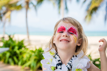 Smiling little girl with vivid face painting. Fancy dress party on the beach.