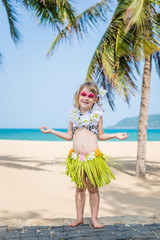 Smiling little girl with  face painting in Hawaiian costume. Fancy dress party on the beach with palms.