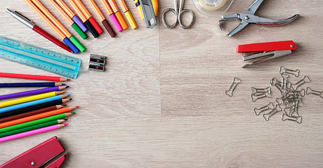 Desktop mockup, top view, with colorful stationery and central copy space, on wooden background