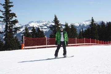 Young snowboard man sliding downhill.