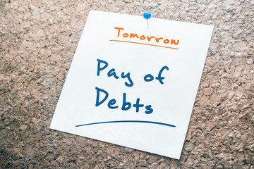 Pay of Debts Reminder For Tomorrow On Paper Pinned On Cork Board