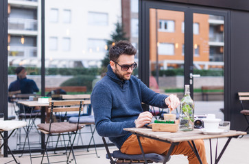 Man in a coffee shop sitting in the terrace outdoors