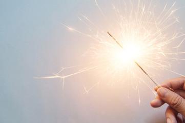man's hand holding a sparkler