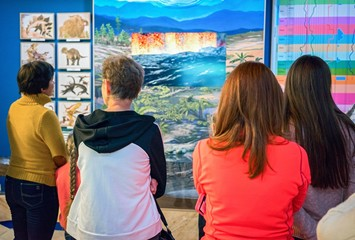 rear view of people looking prehistoric trees and dinosaurus at Baikal Limnological Museum.