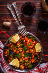 Paella with chicken, chorizo, seafood, vegetables and saffron se