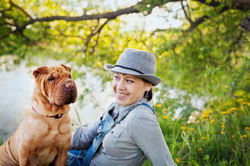 happy young woman in a hat with dog Shar Pei sitting in the field in golden sunset light, true friends forever, people concept