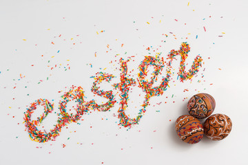 Easter lettering made from colorful baking sugar and colorful hand drawn eggs