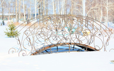 Forged bridge in winter park. Snow on the bridge. Winter walk in the park. The design of the territory.