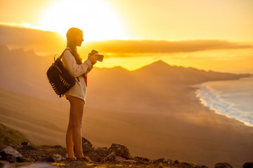 Young female traveler with backpack and photo camera photographing beautiful Cofete coastline with mountains on the sunset on Fuerteventura island in Spain.