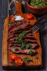 Steak served on a board with salsa verde.