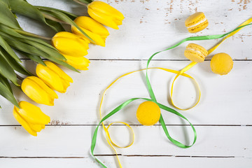 Yellow lemmon macaroons and yellow fresh tulips  on light wooden background