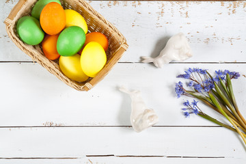 Easter decoration with flowers blue snowdrop, ceramic rabbits and colored eggs over light background