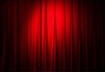 Vintage red velvet curtain with light spots in a concert hall.