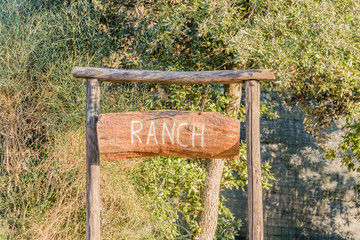 Indication of ranch made with a wooden board and written in white