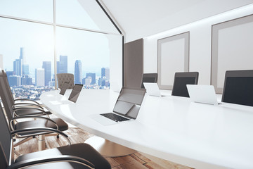 Modern conference room with oval table, chairs, laptops, big win