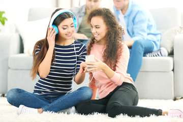 Two teenager girls listening to music with headphones in living room