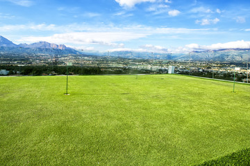 Small golf course amidst beautiful scenery with mountains