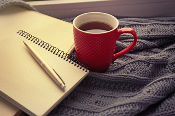 Red cup of tea, book  and warm knitted plaid on windowsill, close up