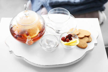 Tea set with lemon and biscuits on a white wooden mat