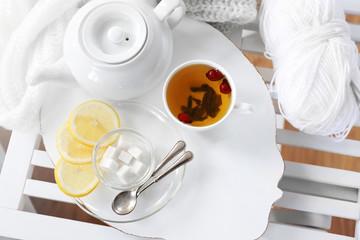 White tea set on a wooden tray on table